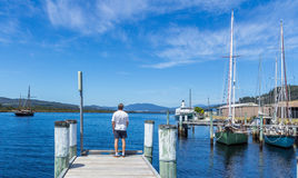 Man standing at the end of a pier on a bright sunny day Stock Images