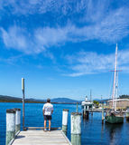 Man standing at the end of a pier on a bright sunny day portrait Stock Photography