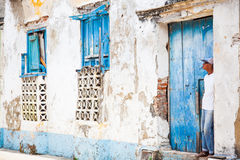 Man standing at the entrance of a dilapidated house. Cartagena, Colombia - August 18, 2011: Man standing at the entrance of a dilapidated house in Getseman Stock Photography