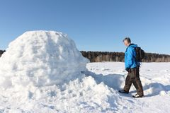 Man standing at the entrance an igloo. On a snowy reservoir in winter, Novosibirsk, Russia Stock Photo