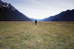 A man standing and facing towards vast empty landscape. Stock Photo