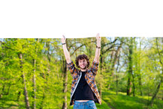 Man standing in a field with a blank sign Stock Photo