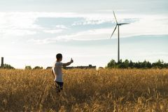 A man standing in a field looking at a wind generator. A man standing in a wheat field looking at a wind generator Royalty Free Stock Photo