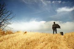 Man standing in a field. Observing the horizon stock image