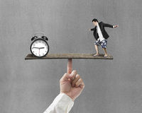 Man standing on finger seesaw vs clock Royalty Free Stock Images