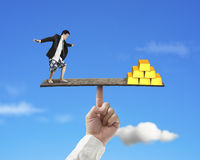 Man standing on finger seesaw vs stack of gold Royalty Free Stock Images