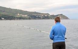 Man standing fishing at the seaside Royalty Free Stock Photo