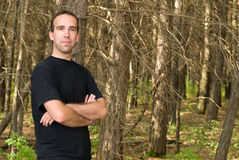 Man Standing In The Forest. A young man standing in the forest with copyspace to the right Stock Photos