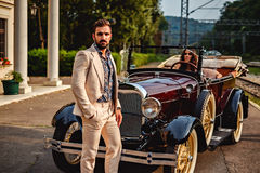 Man standing in fron of a woman in a classic car. Man standing in fron of a women in a classic car. Hot summer day stock photos