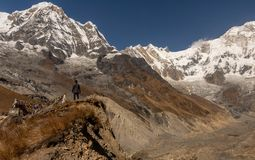 Man standing in front of Annapurna South and Annapurna 1 in Annapurna Base Camp, Himalayas royalty free stock photography