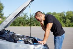 Man standing in front of a broken car. Young man standing in front of a broken car stock photography