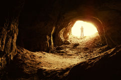 Man standing in front of a cave entrance. A photo taken from inside of a cave, of a man standing in front of the entrance to the cave