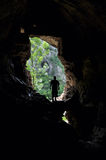Man standing in front of a cave entrance Stock Photography