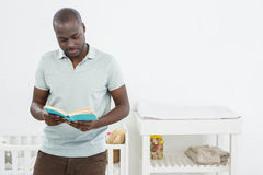 Man standing in front of a cradle and reading a book. Smiling man standing in front of a cradle and reading a book at home Royalty Free Stock Image