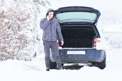 Man standing in front of damaged car and calling car services to royalty free stock photography