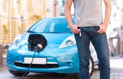 Man standing in front of electric car Stock Photo