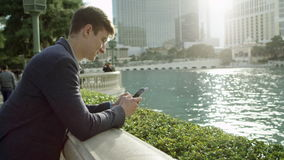 Man is standing in front of fountain at Bellagio and typing a text message. Young handsome is standing alongside a Bellagio fountain in Las Vegas and texting stock video footage