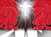 Man standing in front of glowing cross parting a giant wall of huge red question marks. Man standing in front of glowing cross with flowing light beams parting a Royalty Free Stock Image