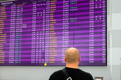 A man is standing in front of information board for arrivals and departures. Information stand at the airport, railway. A man is standing in front of a lilac stock image