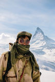 Man standing in front of Matterhorn. A man in camouflage winter coat standing in front of the background of Matterhorn stock image