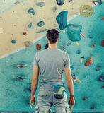 Man standing in front of a practical climbing wall Royalty Free Stock Image