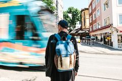 Man standing in front of road with tram. Male tourist in casual clothes with backpack is standing in front of road with Royalty Free Stock Photo