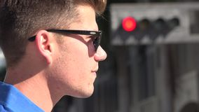 Man Standing in Front of Traffic Signal. Stock video of a man at an intersection stock footage