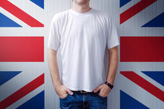 Man standing in front of United Kingdom flag wall. Adult male person supporting Great Britain Royalty Free Stock Images