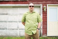 Man standing in front of a weathered garage royalty free stock image