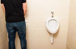 Man standing in front of a white pissoir in bathroom Royalty Free Stock Image