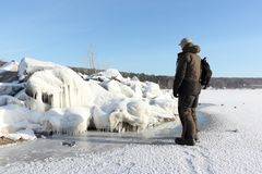 Man standing on a frozen river near stones with icicles Royalty Free Stock Photography