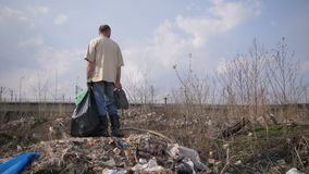 Man standing on garbage hill at landfill site. Mature homeless man in dirty clothes standing on the hill of garbage at trash dump landfill site in city. Male stock video footage