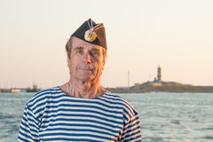 Man standing in garrison cap and striped vest on the background. Man standing in garrison cap and striped vest on a background of sea summer day Stock Photos