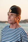 Man standing in garrison cap and striped vest on the background. Man standing in garrison cap and striped vest on a background of sea summer day Royalty Free Stock Photos
