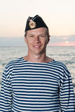 Man standing in garrison cap and striped vest on the background. Man standing in garrison cap and striped vest on a background of sea summer day Stock Image