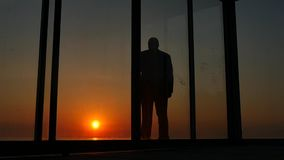 Man standing glass doors of the house at sunset stock video footage