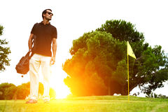 A man standing on a golf course at sunset Stock Images
