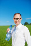 Man standing in a green field drinking water Stock Photography