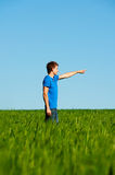 Man standing in green field and pointing Royalty Free Stock Photography