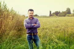 Man standing in green field Stock Photo