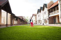 Man is standing on a green lawn of the cottage homes. Stock Photography