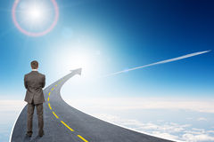 Man standing on grey highway going up as arrow Royalty Free Stock Image