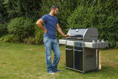 Man standing by a grill Stock Image