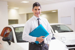 Man standing with hand in pocket while holding folder. At new car showroom stock photography