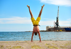 Man standing on hands. Man doing yoga standing on hands. industrial harbor crane background Royalty Free Stock Photo