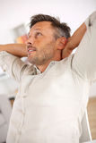 Man standing with hands under head. Man relaxing with outstretched arms behind head Stock Images