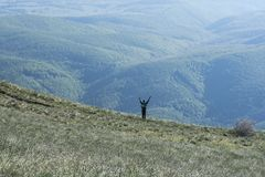 Man standing with hands up on the edge of mountain meadow looking to a valley Stock Images