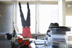 Man standing on head in office Royalty Free Stock Photography