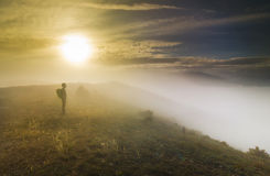 Man standing on a hill in foggy weather at sunset Stock Photo