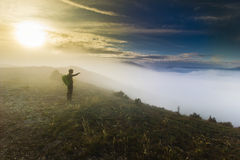 Man standing on a hill in foggy weather at sunset Royalty Free Stock Images